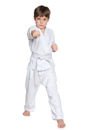 karate boy: A portrait of a serious little boy in kimono on the white background Stock Photo