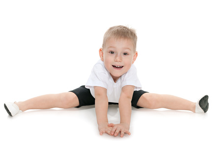 only one boy: Little boy performs gymnastic exercises on the white background Stock Photo
