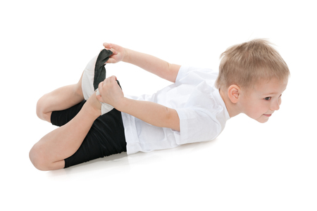 one boy only: A little boy performs gymnastic exercises on the white background Stock Photo