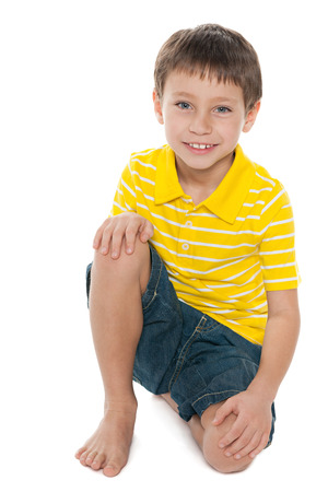 yellow shirt: A portrait of a smiling little boy in the yellow shirt on the white background Stock Photo