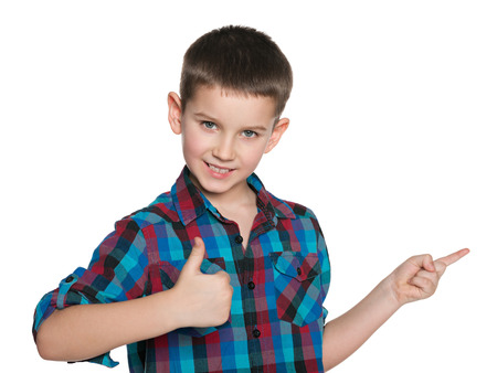 aside: A young boy with his thumb up shows his finger aside on the white background Stock Photo