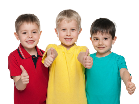 Three joyful boys are standing together on the white background and hold their thumbs up photo