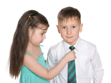 A little girl helps a little boy in a white shirt with a tie Stock Photo