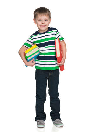 A portrait of a smiling little boy with books against the white  photo