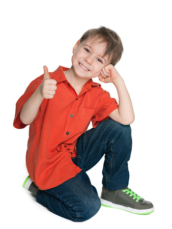 A smiling fashion boy with his thumb up is sitting on the white background Standard-Bild