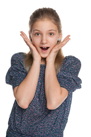 A portrait of a surprised preteen girl on the white background photo