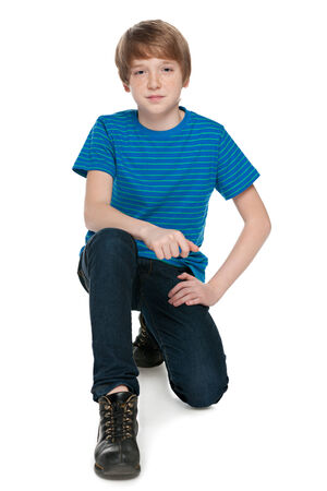 preteen boy: A fashion preteen boy is sitting on the white background Stock Photo