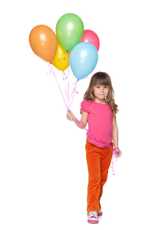 A smiling little girl holds balloons against the white  photo
