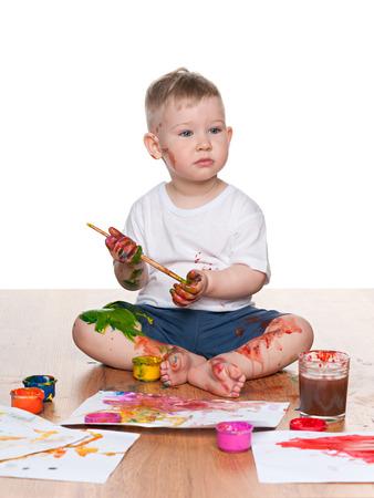 A little boy paints sitting on the floor photo