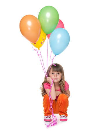 A thoughtful little girl holds balloons against the white  photo