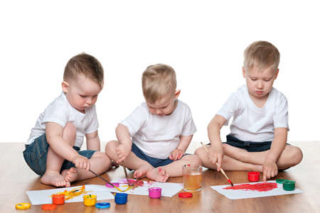 Three little boys paint sitting on the floor photo