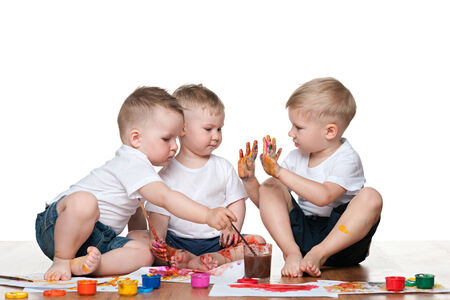 Three little boys sit on the floor and paint photo