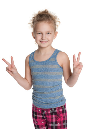 A cheerful young girl shows a victory sign against the white background photo