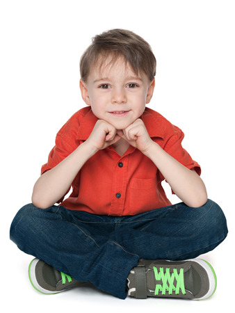 alone boy: A cute thoughtful boy is sitting on the white background