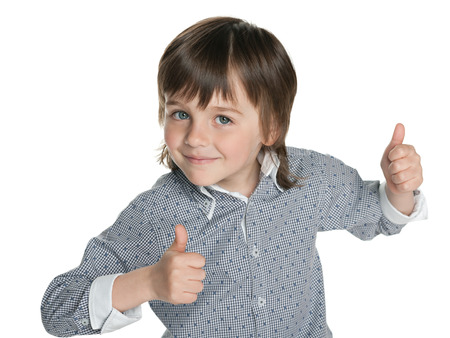 A fashion little boy holds his thumbs up on the white  photo