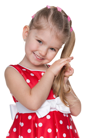 girl in red dress: A portrait of a shy little girl in a red polka dot dress on the white  Stock Photo
