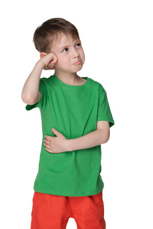 befuddled: A puzzled child in the green shirt is standing against the white