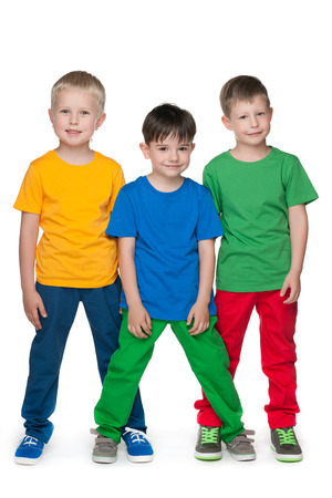 Three little boys are standing together against the white  photo
