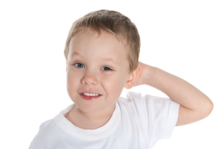 A dreaming preschool boy in the white shirt against the white background photo
