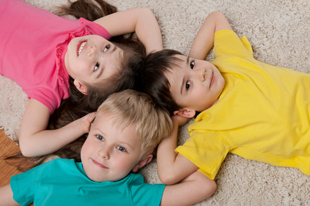 Three happy children are resting on the white carpet photo