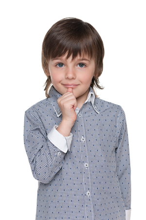 befuddled: A puzzled little boy is standing against the white background