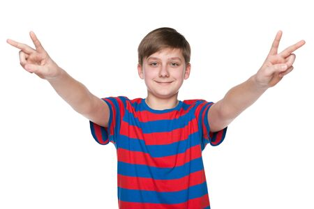 A smiling teen boy shows victory signs against the white background photo