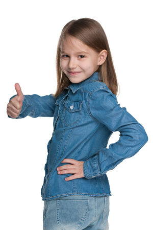 side profile: A little girl holds her thumb up and looks back