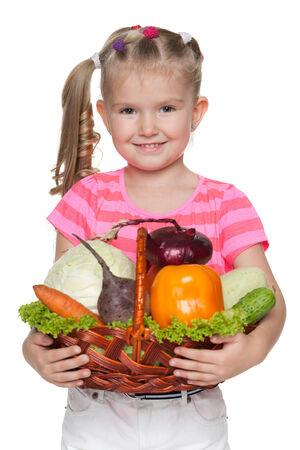 A smiling little girl holds a basket with vegetables photo