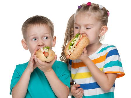 perro comiendo: Dos niños con los perros calientes en el fondo blanco