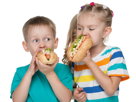 Two children with hot dogs on the white background photo
