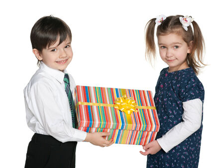Two smiling children hold a gift box against the white background photo
