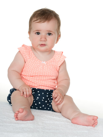 only girls: A cute thoughtful baby girl sits on the white towel