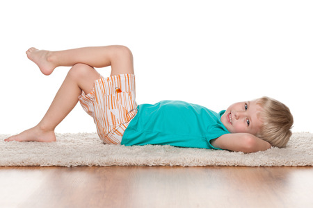 A happy little boy rests on the white carpet Stock Photo