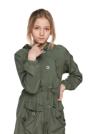 preteen girl: A fashion preteen girl in the green coat on the white background