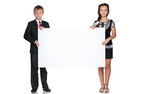 Two happy children hold a white board photo