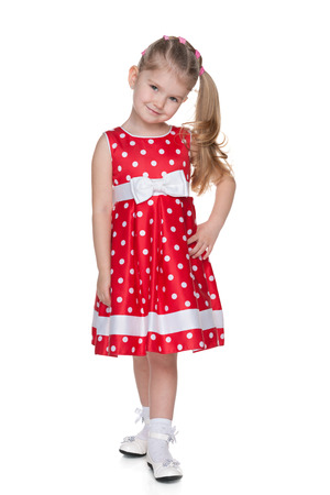 petite fille avec robe: Une jolie petite fille en robe à pois rouge est debout sur le fond blanc Banque d'images