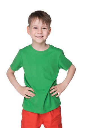 Een portret van een knappe kleine jongen in een groen shirt tegen de witte achtergrond Stockfoto