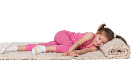A happy little girl rests on the white carpet Stock Photo