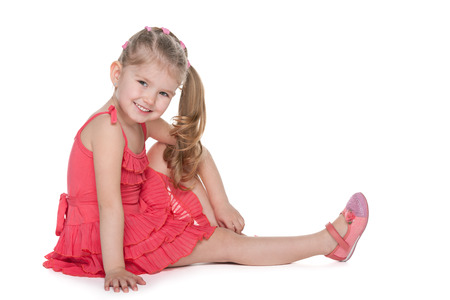 kids dress: An adorable little girl is sitting on the floor on the white background Stock Photo