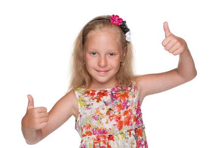mignonne petite fille: Une petite fille mignonne tient ses pouces vers le haut sur le fond blanc
