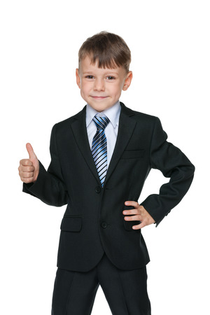 black suit: A school boy holds his thumb up on the white background Stock Photo