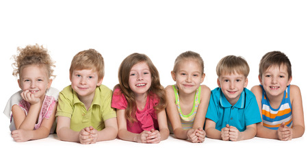 six girl: Group of six smiling children are lying on the floor on the white background Stock Photo