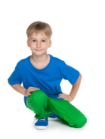 blue jeans kids: A smiling little boy in a blue shirt is sitting on the white background