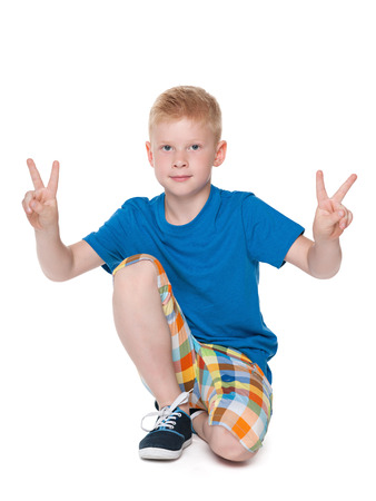A young boy shows a victory sign against the white background photo