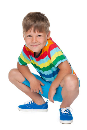 blond boy: A cute little boy sits on the white background