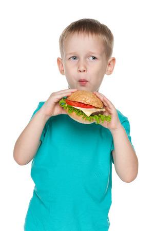 Little boy eats hamburger on the white background photo