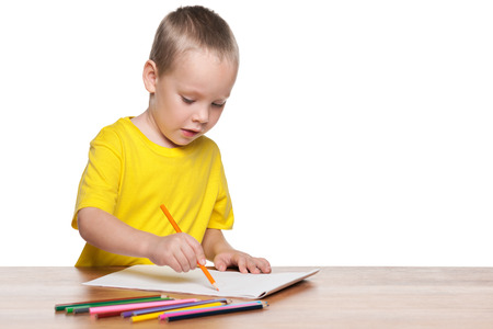 blond boy: A little boy is sitting at the desk and draw