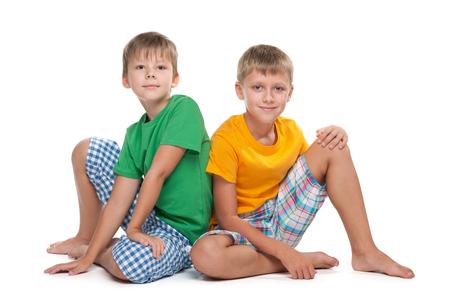 Dos chicos jóvenes y guapos se sientan juntos en el fondo blanco