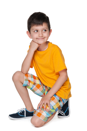A smiling little boy in a yellow shirt is sitting on the white background