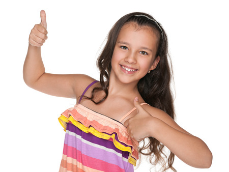 preteen: A happy preteen girl holds her thumbs up on the white background